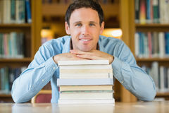 Smiling mature student with stack of books at library desk Stock Images