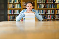 Smiling mature student with stack of books at library desk Stock Photo
