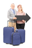 Smiling mature tourists holding a big black arrow and travel bag Royalty Free Stock Image