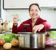 Smiling mature woman adding seasoning into  soup pan Stock Photography