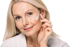 Smiling mature woman applying cosmetic cream. Isolated on white royalty free stock image