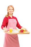 A smiling mature woman in apron carrying a tray with drinks and Stock Photo