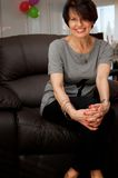 Smiling mature woman on armchair stock photography