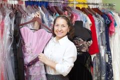 Smiling mature woman chooses  dress Stock Photos