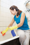 Smiling mature woman cleans bathtub Stock Photo