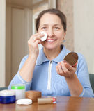 Smiling mature woman cleans the make-up Royalty Free Stock Images