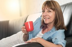 Mature woman during coffee break at home, light effect. Smiling mature woman during coffee break at home, light effect Royalty Free Stock Photo