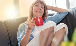 Mature woman during coffee break at home, light effect. Smiling mature woman during coffee break at home, light effect Royalty Free Stock Images