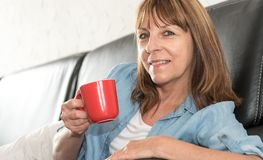 Mature woman during coffee break at home. Smiling mature woman during coffee break at home Royalty Free Stock Photos
