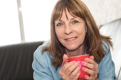 Mature woman during coffee break at home. Smiling mature woman during coffee break at home Stock Photo