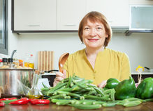 Smiling mature woman cooking okra Royalty Free Stock Photos