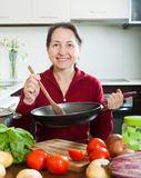 Smiling mature woman cooking  with skillet Royalty Free Stock Images