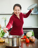 Smiling mature woman cooking soup Stock Images