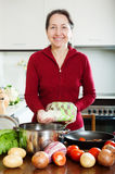 Smiling mature woman cooking soup with rice Stock Image