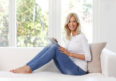 Smiling mature woman with digital tablet. Full length portrait of smiling woman with digital tablet. Beautiful female sitting at home on sofa and touching the Royalty Free Stock Images