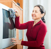 Smiling mature woman dusting TV Royalty Free Stock Images