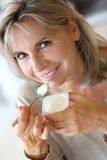Smiling mature woman eating yogurt with spoon royalty free stock images