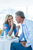 Smiling mature woman feeding food to man Royalty Free Stock Photos