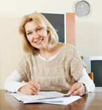 Smiling mature woman filling in paper Stock Photography