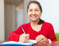 Smiling mature woman fills in documents Stock Photo