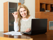 Smiling mature woman fills in the questionnaire in laptop Royalty Free Stock Images
