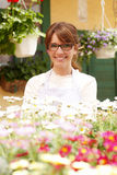 Smiling Mature Woman Florist  At Flower Shop Royalty Free Stock Photography