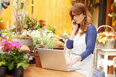 Smiling Mature Woman Florist Small Business Flower Shop Owner. She is using her telephone and laptop to take orders for her store. Shallow Focus royalty free stock photo