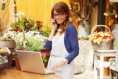 Smiling Mature Woman Florist Small Business Flower Shop Owner. She is using her telephone and laptop to take orders for her store. Shallow Focus Royalty Free Stock Images