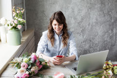 Smiling Mature Woman Florist Small Business Flower Shop Owner. She is using her telephone and laptop to take orders for. Her store. selective Focus stock photography