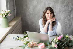 Smiling Mature Woman Florist Small Business Flower Shop Owner. She is using her telephone and laptop to take orders for Royalty Free Stock Photo