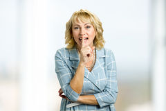 Smiling mature woman gesturing silence. Middle aged woman making silence gesture, shhhhh. Keep the silence gesture Stock Image