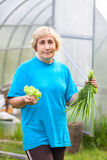 Smiling mature woman with green-stuff Stock Photos