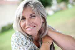 Smiling mature woman with grey long hair outdoor Stock Image