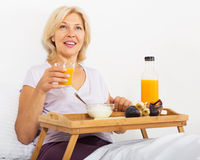 Smiling mature woman having   breakfast in bed Stock Photos