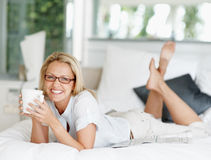 Smiling mature woman having coffee lying in bed Royalty Free Stock Photos