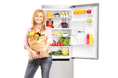Smiling mature woman holding a bag full of groceries. Smiling mature woman holding a paper bag full of groceries in front of refrigerator, isolated on white Stock Image