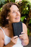 Smiling mature woman holding bible Stock Photos