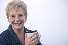 Smiling mature woman holding a cup of coffee stock photos