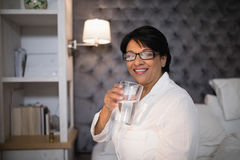 Smiling mature woman holding water glass in bedroom at home Stock Image