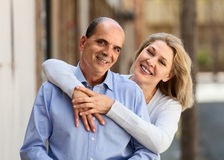 Smiling mature woman hugging man while walking Royalty Free Stock Image