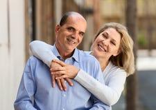Smiling mature woman hugging man while walking Royalty Free Stock Image