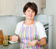 Smiling mature woman kitchen Stock Photo
