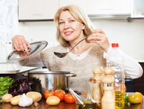 Smiling  mature woman with ladle cooking soup in pan at kitchen Royalty Free Stock Image