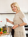 Smiling mature  woman  with ladle cooking soup in pan  in kitchen Royalty Free Stock Image