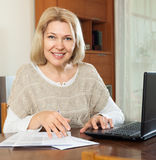 Smiling mature woman with laptop Royalty Free Stock Photos