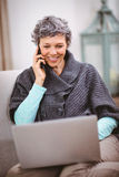 Smiling mature woman with laptop using mobile phone Stock Photography