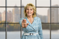 Smiling mature woman making gesture stop. Royalty Free Stock Image