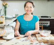 Smiling mature woman making meat dumplings Royalty Free Stock Image