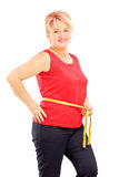 Smiling mature woman measuring her waist after diet Royalty Free Stock Photography