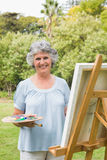 Smiling mature woman painting on canvas stock image